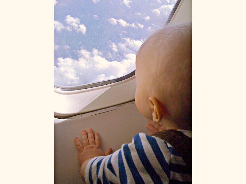 飛行機の外を眺める赤ちゃん