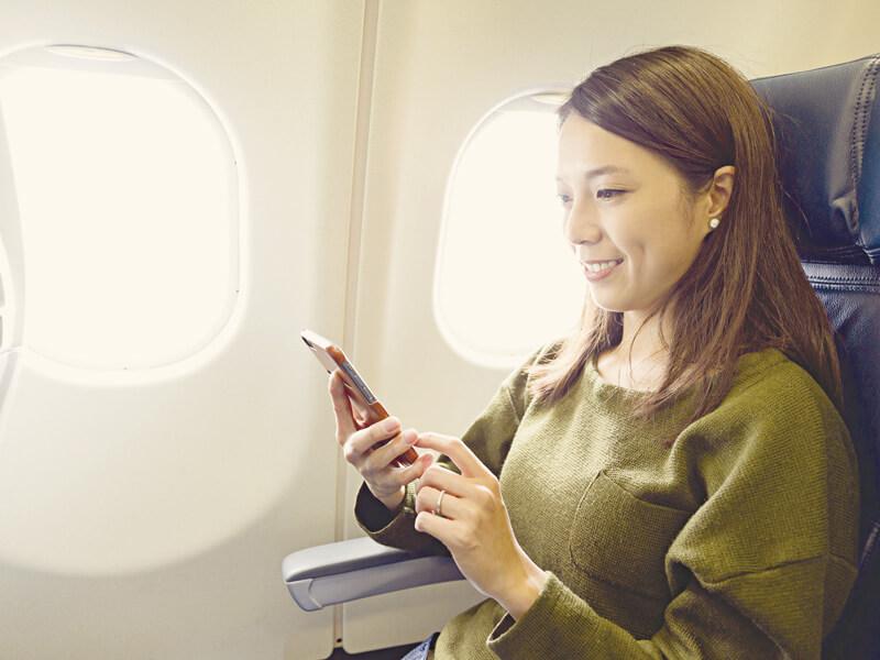 機内でスマホをいじる女性