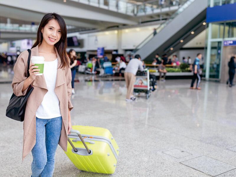 手荷物を持って微笑む女性