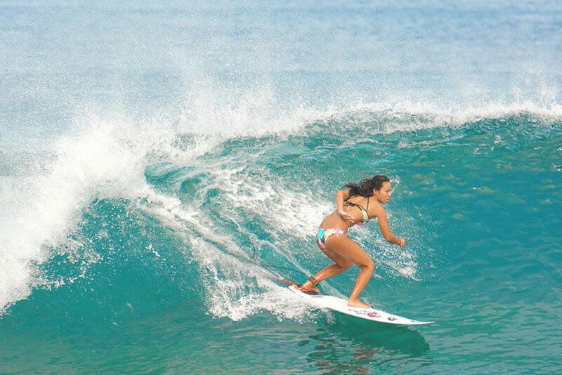 ノースショアでサーフィンする女性