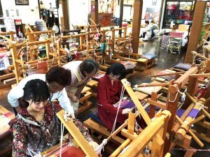 南部裂織の制作体験。左から宮崎香蓮、小島藤子 ©TBS