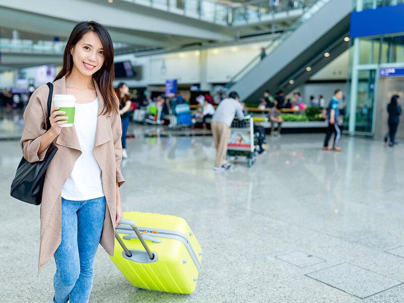 空港でコーヒーを持つ女性