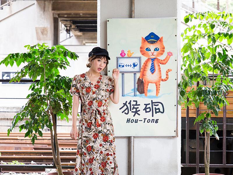 看板の前でファニーな表情の田中里奈さん