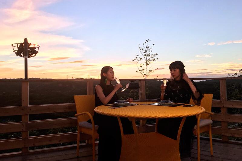 夕陽を眺めながらのディナー。左から田辺かほ、鈴木優華 ©TBS
