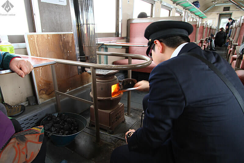 津軽鉄道 ストーブ列車・石炭をくべる車掌さん
