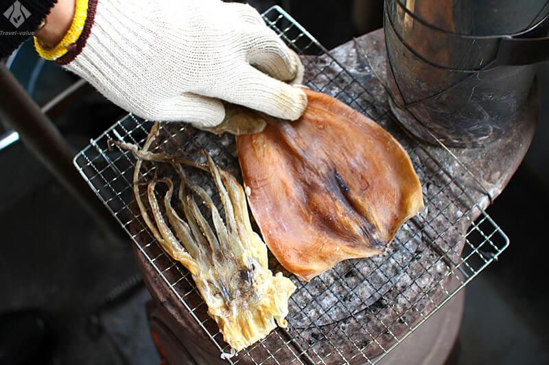 ダルマストーブでスルメを焼くアテンダント