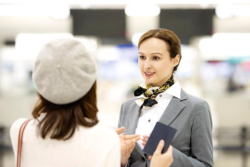 空港で係員と会話する女性(イメージ)