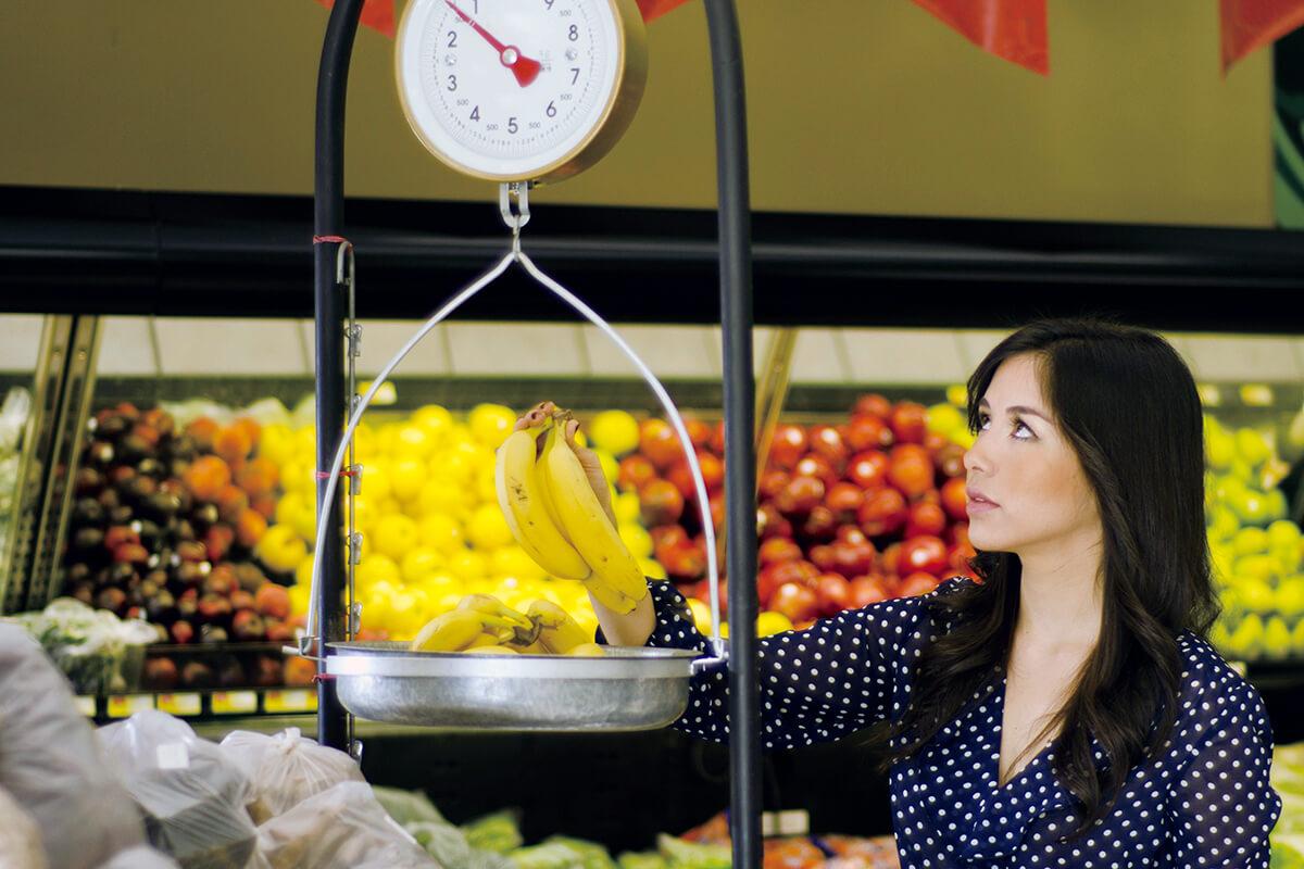 スーパーマーケットでバナナを量る女性