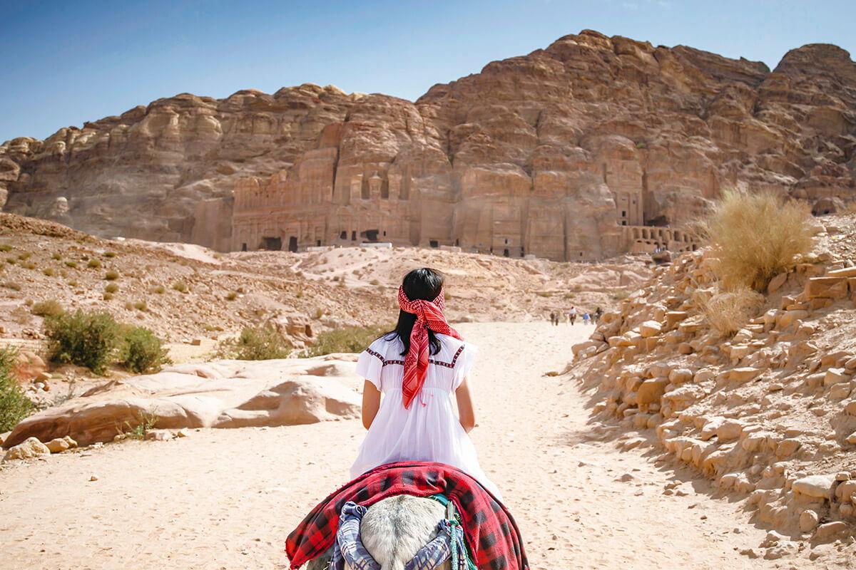 ペトラ遺跡でロバに乗る女性(イメージ)